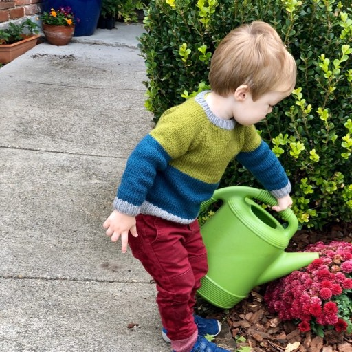 Toddler with a watering can wearing a hand-knit color-block sweater.