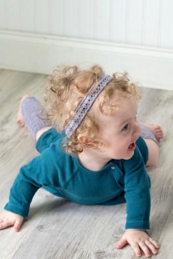 Crawling baby wearing matching hand-knit leg warmers and headband.