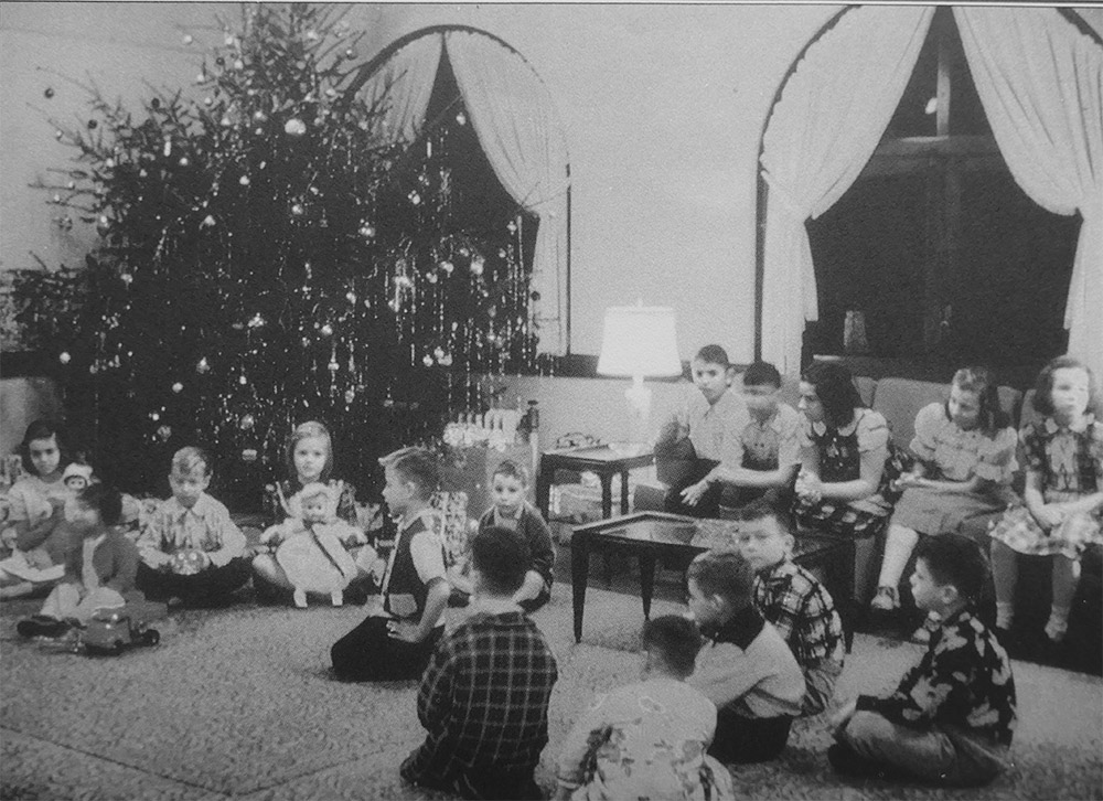 vintage photo of kids with gifts in front of a Christmas tree