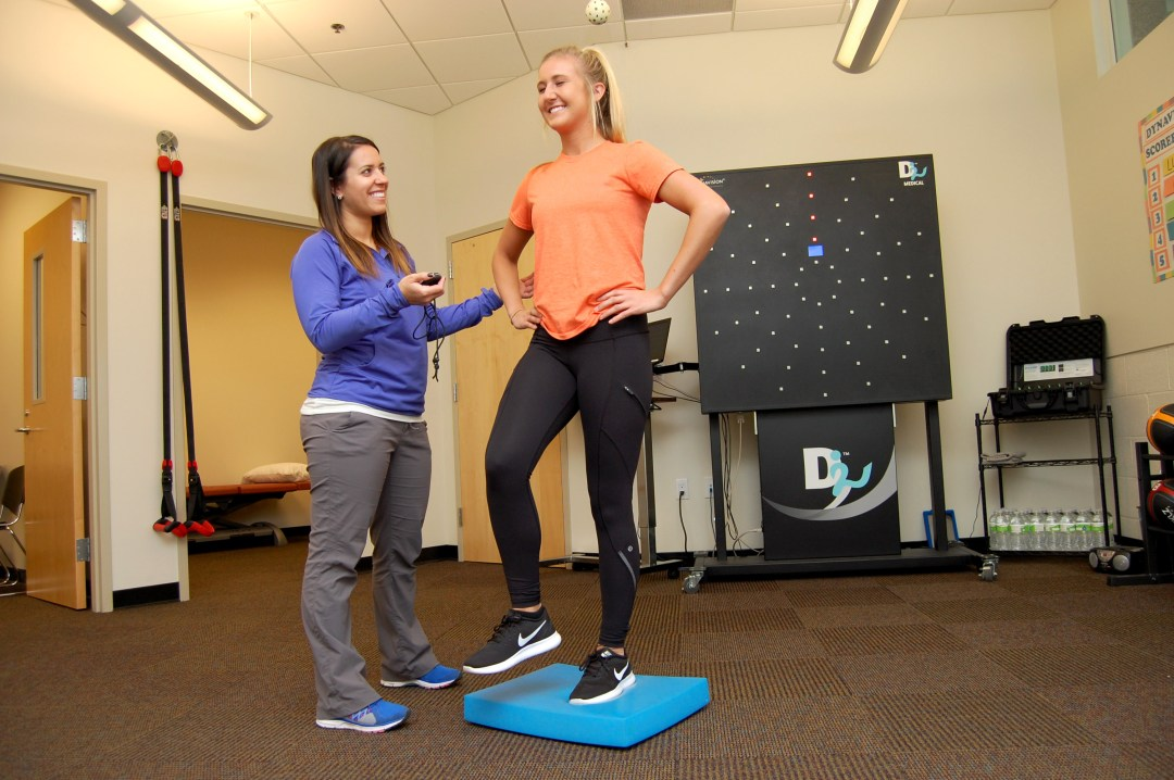 Female teen working on balance with staff