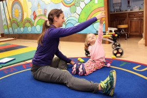 Physical therapist holds toy for child to reach for.