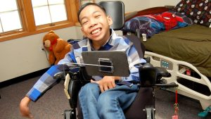 Aim smiling while sitting in his wheel chair