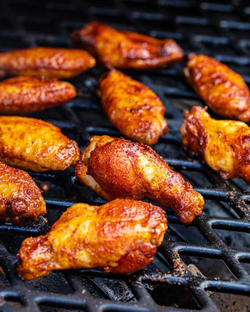 spicy, glowing wings with maple sriracha seasoning on the smoker