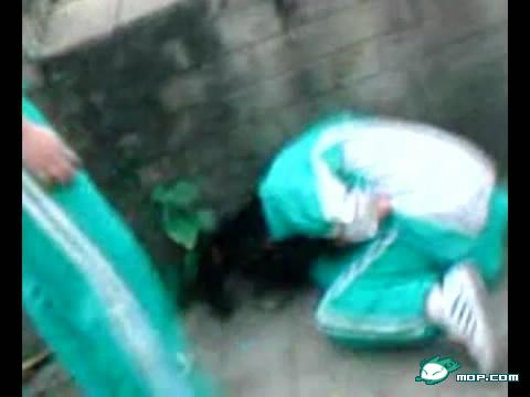 A screen capture of a video where a Cantonese girl in a school uniform is bent over after being beaten by her classmates for stealing.