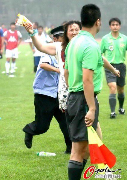 An angry female fan at a football game in Dalian, China chases and attacks a referee.