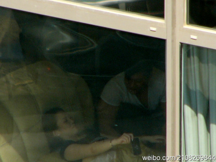 A Chinese man and woman as seen through an apartment window.