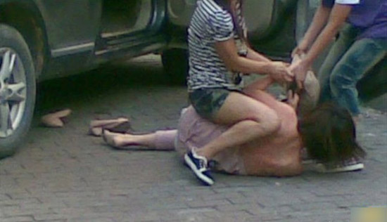A Chinese wife attacks her unfaithful husband's mistress on a street in Guangzhou, China.
