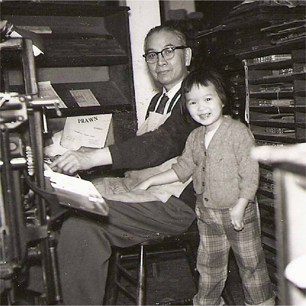 A black and white picture of an older man sitting and a child standing beside him. The man seems to be doing some type of work and has his hand on the desk and is looking at the camera smiling. The child has her hand on the mans legs and looks like she is mid-walk but is looking at the camera