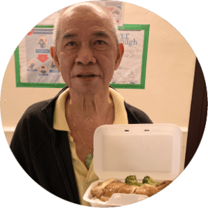 Older bald chinese man standing looking at the camera holding some food
