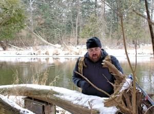 Mike examines tracks atop a fallen cedar tree