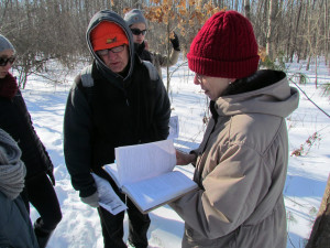 """Cathy Murray checks """"Michigan Trees,"""" one of the recommended books to help with an identification"""