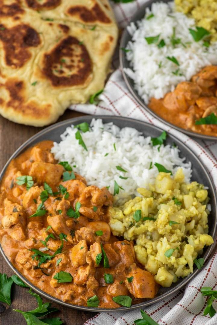 chicken tikka masala with rice and aloo gobi on slate grey plate