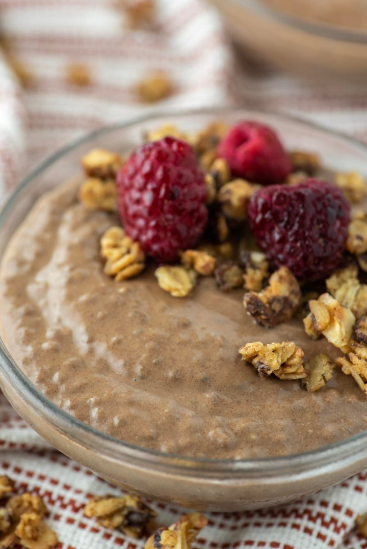 chocolate chia seed pudding in glass bowl with granola and raspberries