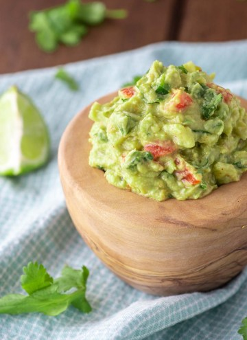 close-up of authentic guacamole in wooden bowl
