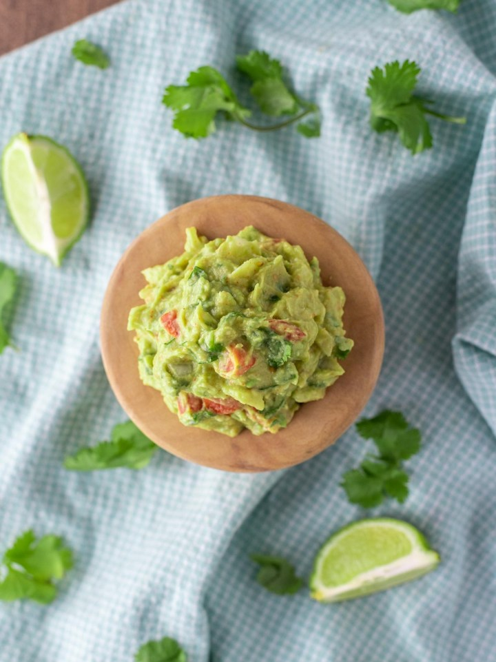 overhead shot of authentic guacamole in wooden bowl