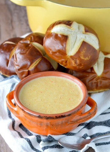 close-up of beer cheese soup recipe in orange bowl with pretzels