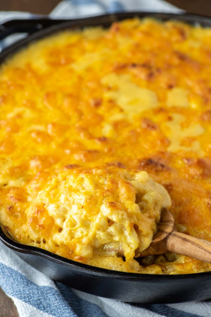 spoon dipped in baked cheddar mac and cheese in skillet