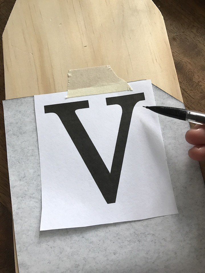 sheet of paper with v over carbon paper on wood