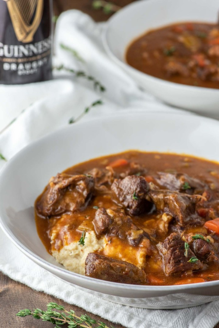 angled shot of Guinness beef stew in white bowl with beer can in background