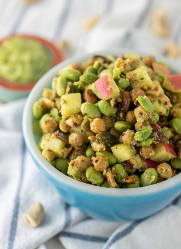 edamame salad in blue bowl with side of avocado dressing
