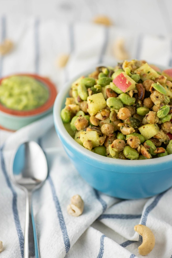 edamame salad in bowl with side of dressing