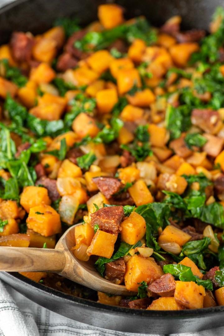 spoon dipped in chorizo sweet potato hash in skillet