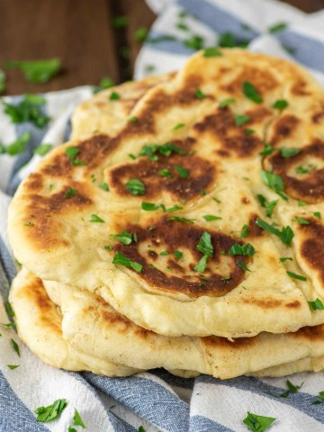 stacked homemade naan on dish towel