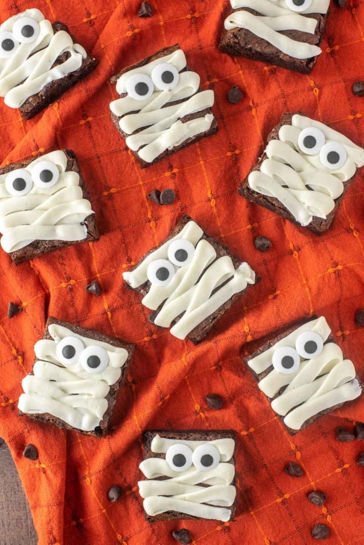 overhead shot of mummy brownies on orange dish towel