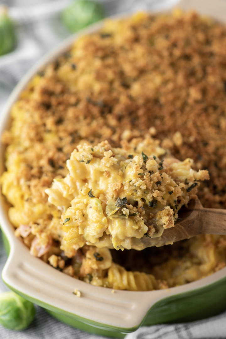 spoon lifting out butternut squash mac and cheese from baking dish