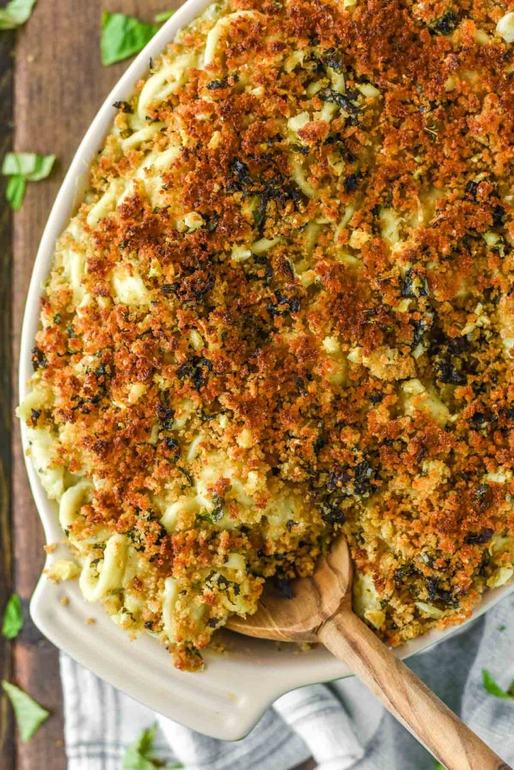 overhead shot of pesto goat cheese mac and cheese in orange bowl and baking dish