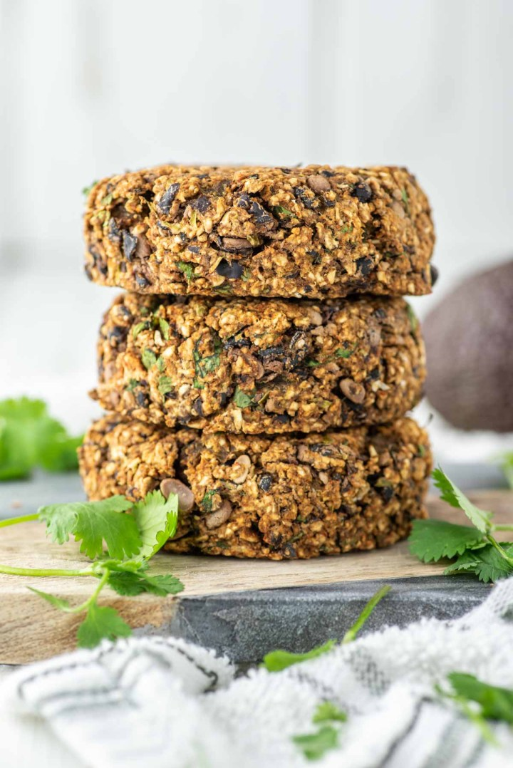 3 stacked black bean burgers on cutting board with cilantro