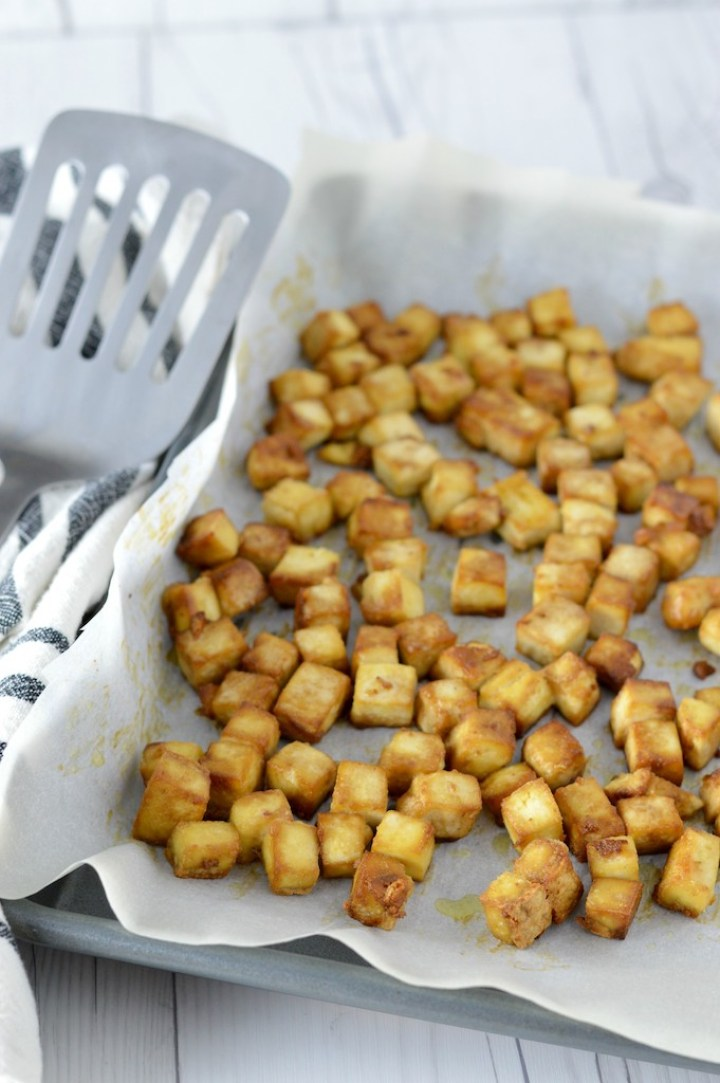close-up of crispy baked tofu in baking sheet with spatula