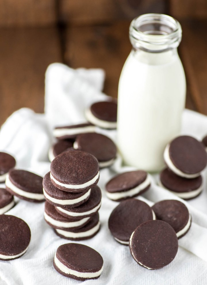 close-up of stacked oreos on white kitchen towel with glass of milk
