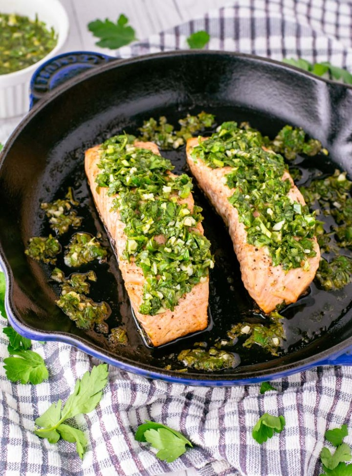 close-up of salmon with chimichurri in skillet