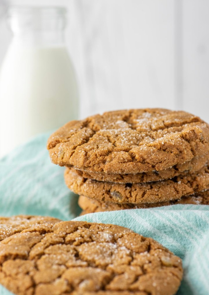 stacked ginger cookies on teal dish towel with glass of milk