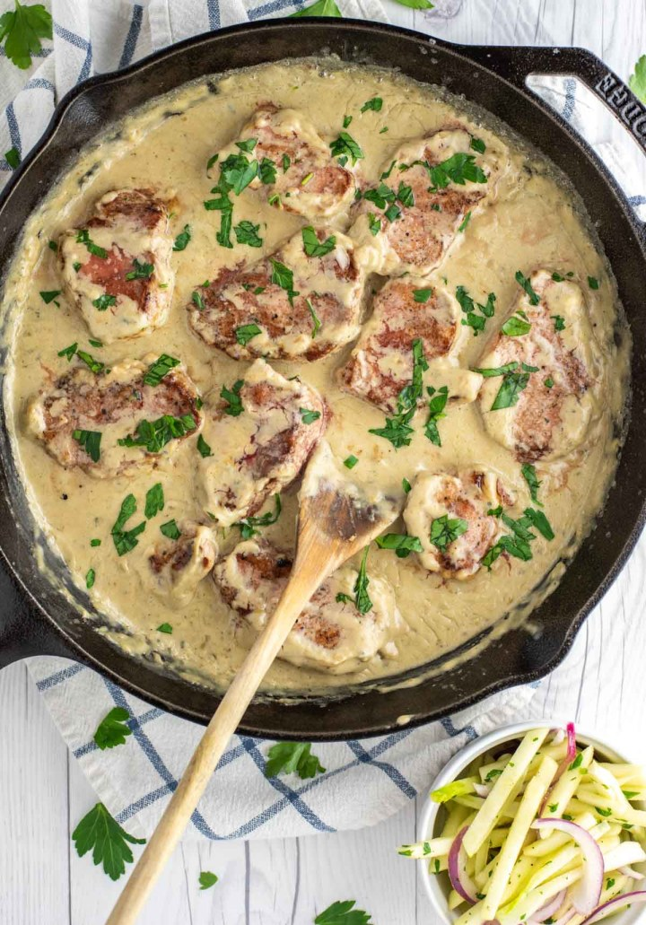 overhead shot of pork medallions with blue cheese sauce in cast iron skillet