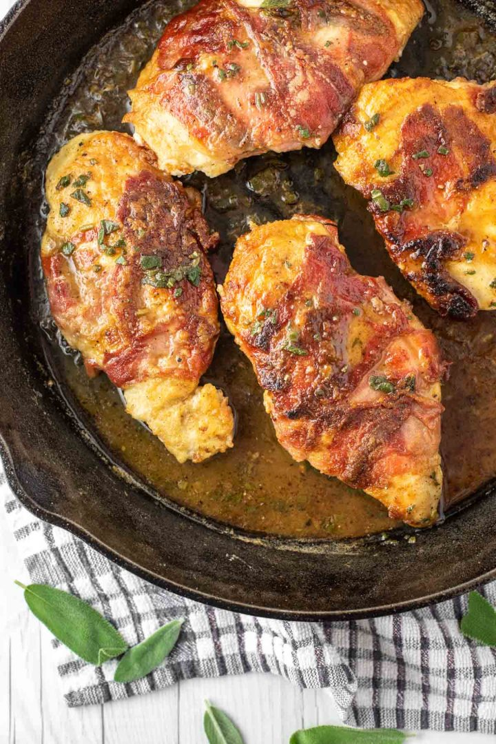 overhead shot of chicken saltimbocca in skillet with wine butter sauce
