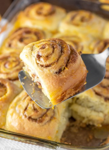 orange roll on spatula above rolls in baking dish