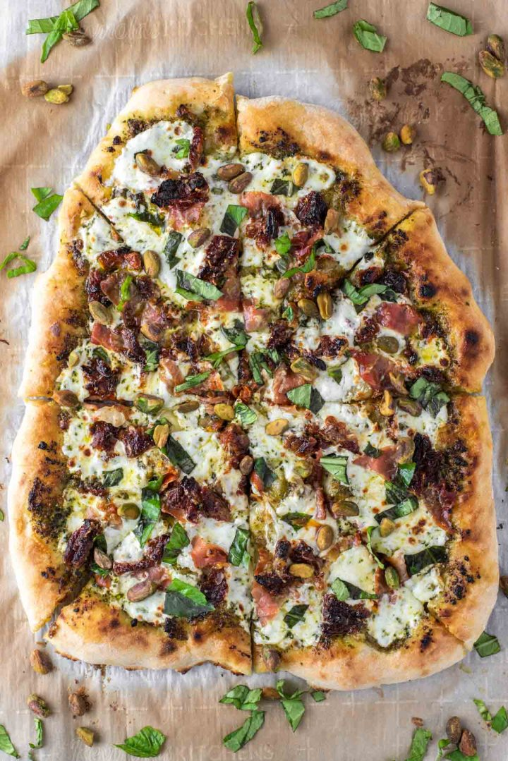 overhead shot of sun-dried tomato prosciutto pesto pizza
