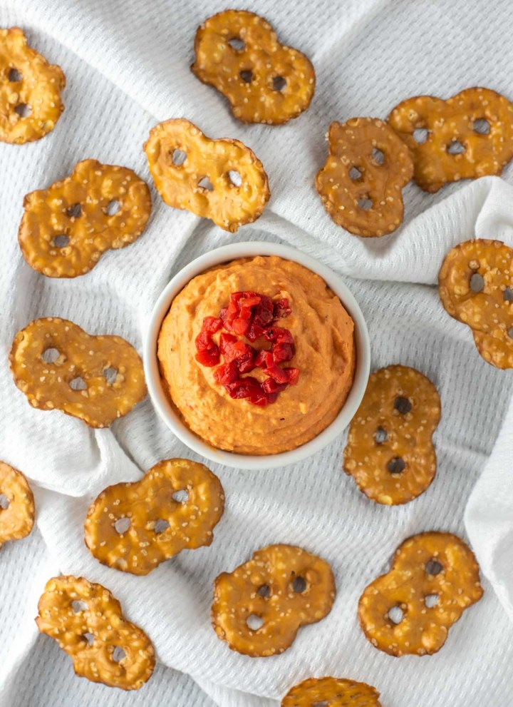 overhead shot of roasted red pepper hummus in white ramiken