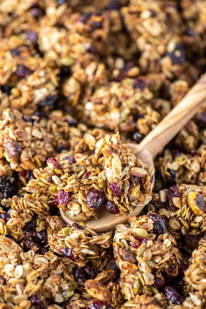 wooden spoon scooping out fruit and nut granola