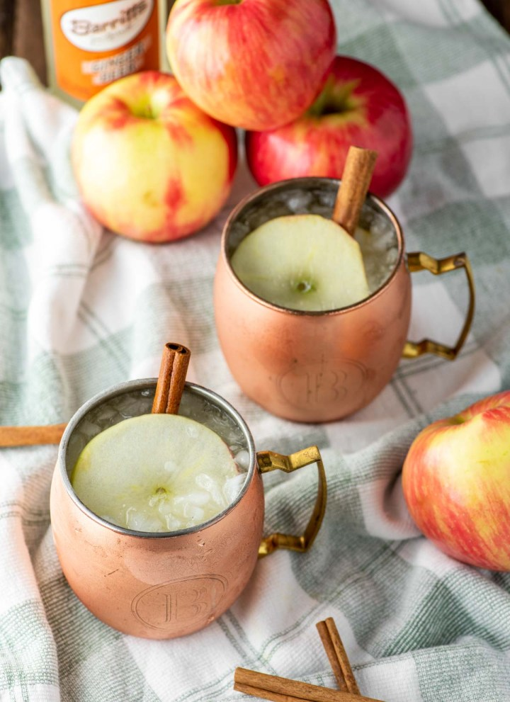 two apple cider moscow mules in copper cups on dish towel