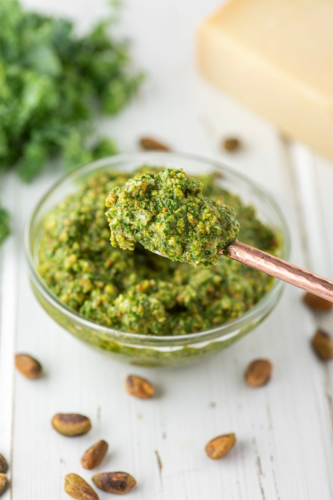spoon lifting out of kale pistachio pesto in glass bowl