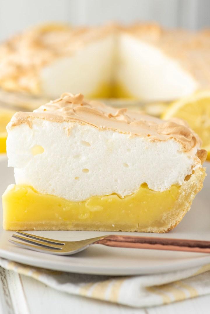 slice of lemon meringue pie with fork on plate