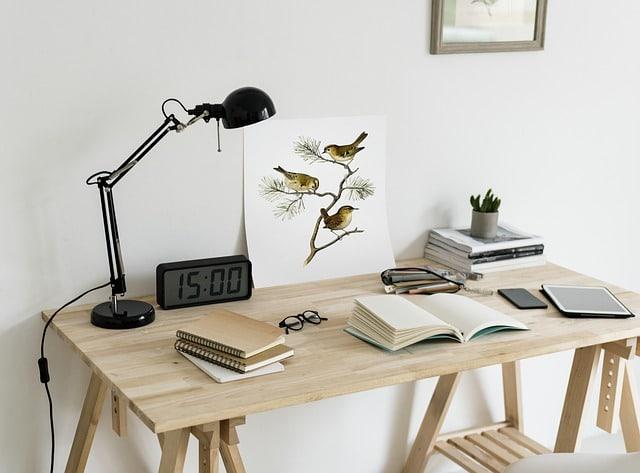 テーブルの上にある開かれた本や文房具、スタンド、時計