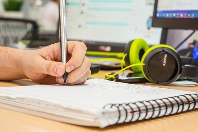 ノートにメモをしている男性の左手