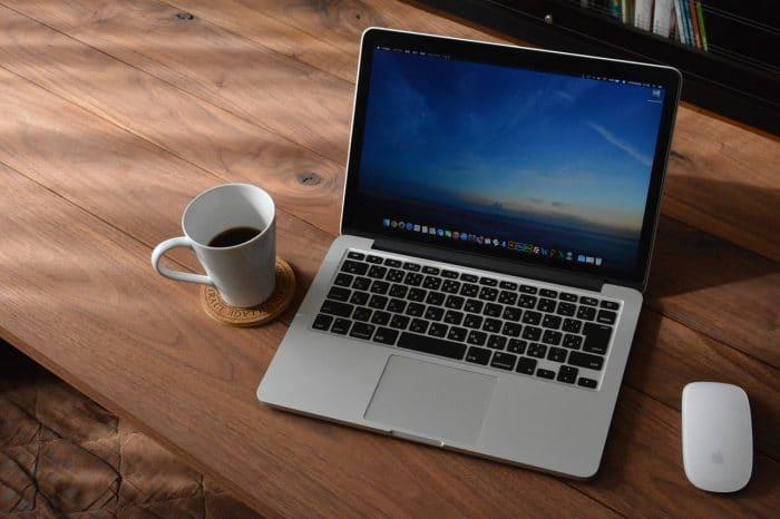 机の上にあるコーヒーとノートパソコンとマウス