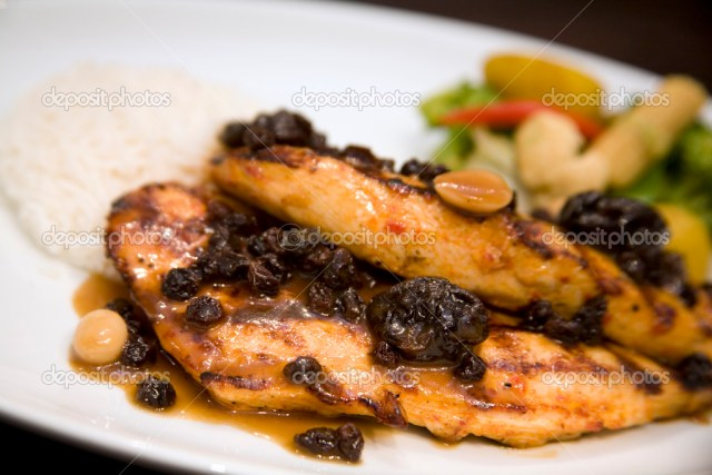 A dish of honey glazed roasted chicken breast with rice and vegetables.