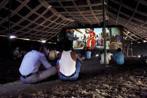 Cinemagoers watch a Bollywood film inside a tent cinema in Pusegaon