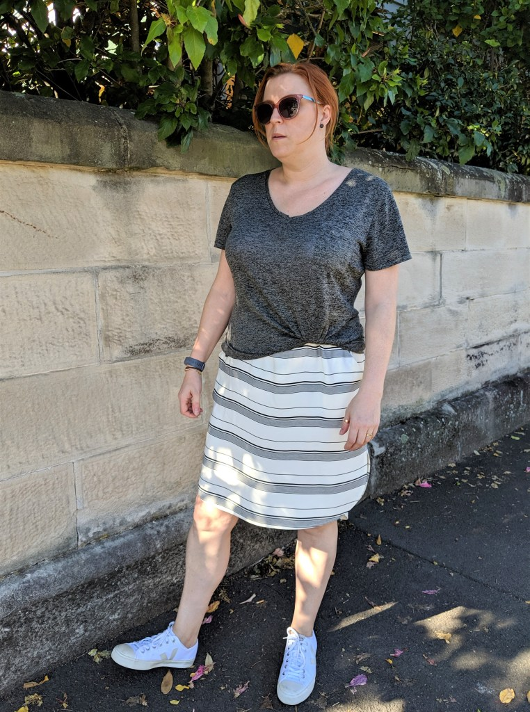 The author standing in front of a sandstone wall.  She is wearing a striped skirt, white shoes and a grey t-shirt.